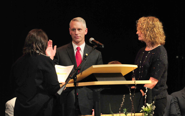 Amesbury: Mayor Thatcher Kezer is sworn is by town clerk Bonnijo Kitchin with his wife, Claire, right, and son, Thatcher, out of view, last night at the Amesbury High School auditorium. Bryan Eaton/Staff Photo