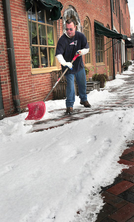 Newburyport: Bob Nolan, who works for Colby Farm which contracts with some businesses in downtown Newburyport to clear snow, cleans the sidewalks in Market Square yesterday morning. Most of the snow will have melted by sun or rain by this morning. Bryan Eaton/Staff Photo