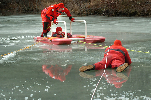 Newburyport: A dozen Newburyport firefighters practiced ice rescue yesterday morning as a refresher excercise is ponds and lakes in the area aren't sufficiently frozen for recreational activity. John Pivetti, top, acts as rescuer to Jay Lowrey as Lt. Stephen Hamilton provides support. Bryan Eaton/Staff Photo