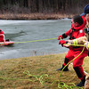"Newburyport: Newburyport firefighters Tony Raven, right, and Paul Dubois pull to safety ""rescuer"" John Pivetti and ""victim"" Jay Lowry at the Spring Hill Pumping Station yesterday. The department was practicing their ice rescue procedures as the ice in the area is really not safe for activity. Bryan Eaton/Staff Photo"