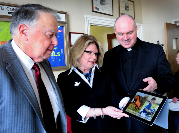 Newburyport: Immaculate Conception alumni Curt Gerrish, left, looks over one of the Apple iPad2's he donated to the school with principal Mary Reardon and Rev. Timothy A. Harrison. Bryan Eaton/Staff Photo