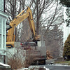 Newbury: Heavy equipment demolished an early 19th century carriage barn yesterday with plans to also tear down at 12-room Federalist  home, left, to make way for a swimming pool. Bryan Eaton/Staff Photo