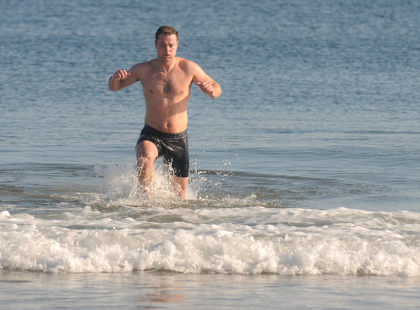 Salisbury: Nate Keliher of Amesbury heads out of the cold waters off Salisbury Beach. Keliher took a swim after running the Hang Over Classic Road Race. Jim Vaiknoras/staff photo