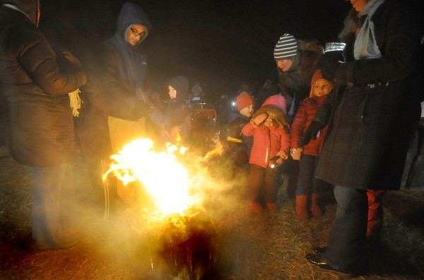 Newbury: Families warm themselves around a small wood fire at the Annual Town of Newbury Christmas Tree Bon Fire at the SpencerPierce Little Farm Saturday night. Jim Vaiknoras/staff photo