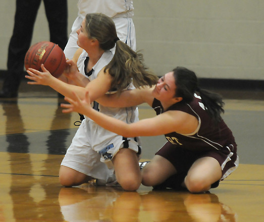 Byfield: Triton'sAmanda Colpitts looks to pass from her knees while being defended by  Rockport's Gabby Muniz during their game at Triton Friday night. Jim Vaiknoras/staff photo