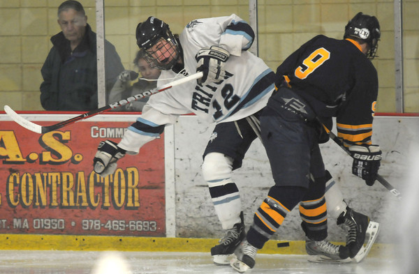 Newburyport: Triton's Nate Williamson gets knocked off the puck by Lynnfield's Dylan Costa during their game at the Graf Rink in Newburyport Saturday. Jim Vaiknoras/staff photo