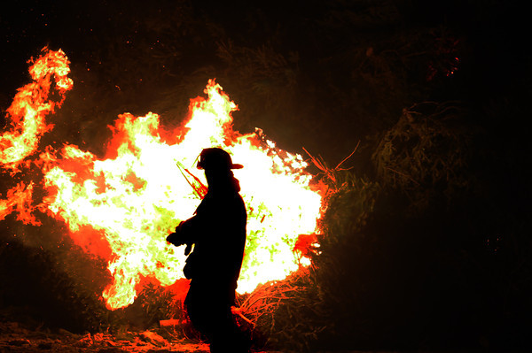 Newbury: A Newbury firefighter walks by the Annual Town of Newbury Christmas Tree bon fire Saturday night at the Spencer Pierce Little Farm. JIm VAiknoras/staff photo