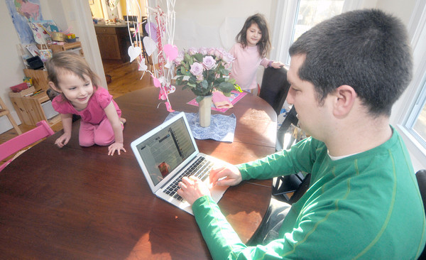 Newburyport: Josh Porter updates his twitter account at his dining room table with some help from his daughters Taia, 2, and Tessa, 3. JIm Vaiknoras/staff photo