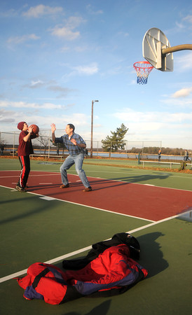 Newburyport: Conner Goodwin get ready to take a shot over his dad Tom during a game of basketball at Cashman Park. With the temperatures in the 50's coats were left on the sidelines. Jim Vaiknoras/staff photo