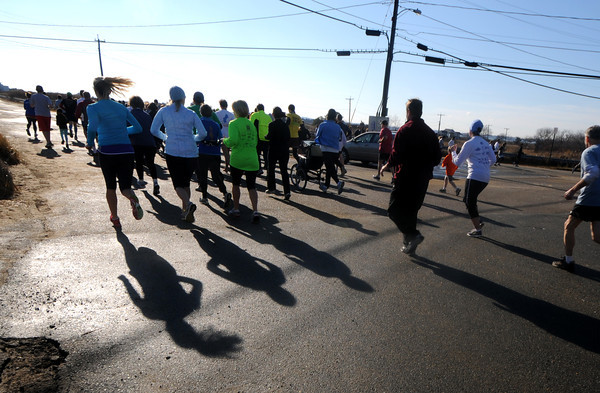 Salisbury: Runner cast long shadows on Atlantic ave in Salisbury as the the Hang Over Classic Road Race on a sunny warm New Years day. Jim Vaiknoras/staff photo
