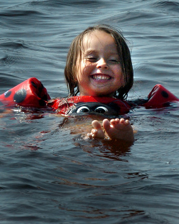 Amesbury: Natalee Pena, 3, shows off her skills at swimming, which she just started to learn, by lifting her toes out of the water. The Amesbury youngster was cooling off with her family yesterday at Lake Gardner Beach in Amesbury. Bryan Eaton/Staff Photo