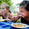 Salisbury: Payton Baker, 10, left of Newburyport and Lindsey Gardella, 11, of Salisbury dig into some pasta salad at the Salisbury Community Garden at a cookout there for supporters. The two are part of the team from the Boys and Girls Club who have a plot there and where the cucumbers came from for the salad. Bryan Eaton/Staff Photo