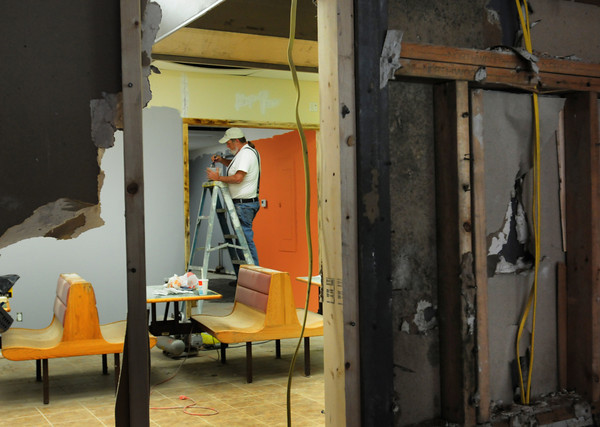 Amesbury: A friend of Bergeron, Jeff Witham does some painting seen through a break in the wall, which is coming down to create a larger space for the businesses. Bryan Eaton/Staff Photo