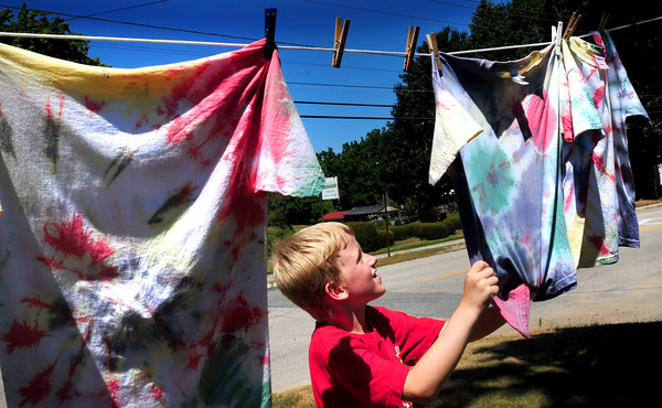 Amesbury: Trevor Kimball, 7, grabs his t-shirt after letting it dry in the breeze at Amesbury Town Park. The children in the summer program there were making their own tie dye shirts on Wednesday afternoon. Bryan Eaton/Staff Photo