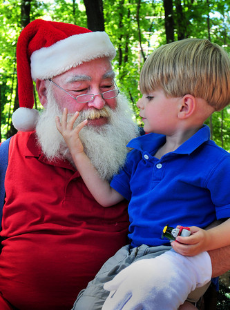 Amesbury: Parker Castro, 3, of Newburyport gives Santa Claus' beard a tug to see if he's the real Santa, which, of course, he was. They were at the Newburyport Mother's Club Christmas in July at Hodgies Ice Cream in Amesbury collecting toys for needy children in exchange for an ice cream sundae. Bryan Eaton/Staff Photo