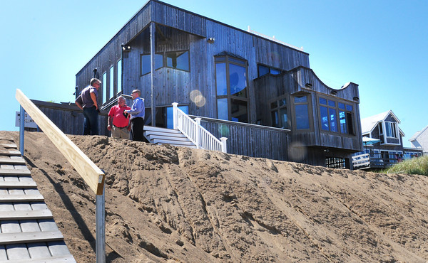 Newbury: Tom Nee, left, meets with Newbury selectman Joe Story and DJ Napolitano from Congressman Tierney's office at Nee's 37 Annapolis Way home on Plum Island. Nee has put in sand as an emergency measure to new erosion problems. Bryan Eaton/Staff Photo