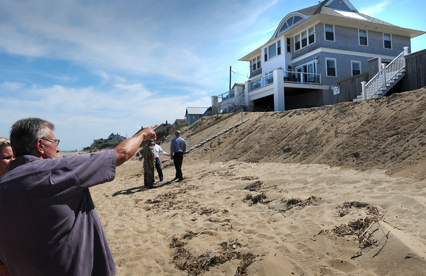 Newbury: Tom Nee gestures to the sand that's replenished eroded beachfront to Bob Connors' home, left, and his to right, the stairs showing. Bryan Eaton/Staff Photo