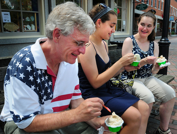 Newburyport: Wearing a patriotic shirt Jeff Morrill enjoys an icy treat in downtown Newburyport with his daughter, Diana, and wife Joyce on the Fourth of July. The family is from, fittingly, Lexington where the American Revolution started. Bryan Eaton/Staff Photo
