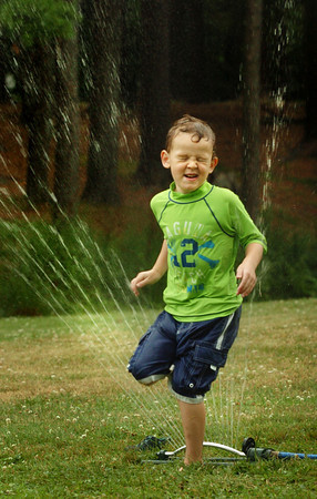 Amesbury: Water was the theme of the day at Amesbury Recreation Department's summer camp at the town park as temperatures reached the 90's. Henry Smith, 4, ran through the sprinkler many times to cool off. Bryan Eaton/Staff Photo