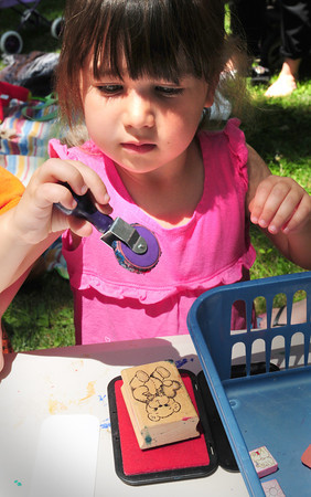Amesbury: Lauren Stewart, 3, of Andover chooses a wheel of mini Teddy Bear imprints to make a book marker at the Teddy Bear Picnic at the Amesbury Public Library on Wednesday. She was visiting her grandmother, Sandy Stewart who lives nearby for the event, one of several for children during the summer. Bryan Eaton/Staff Photo