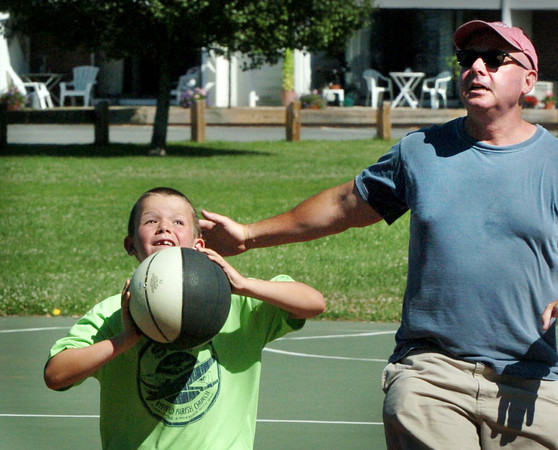 Newburyport: Charlie Grossman, 8, of Newburyport moves around his father, Charlie, to make a shot yesterday afternoon. The two were playing a little one-on-one at Cashman Park in Newburyport. Bryan Eaton/Staff Photo