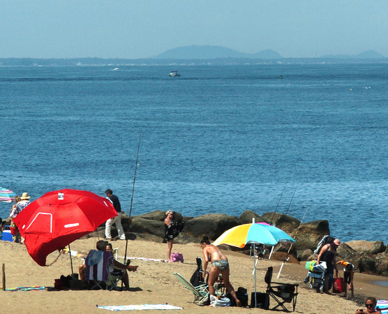 Newbury: Mount Agamenticus in York, Maine can be seen over these beachgoers near Plum Island center Wednesday afternoon. Bryan Eaton/Staff Photo