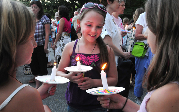 Merrimac: Alyssa Coberly, 9, center, lit the candles of friends Faith Haberland, 8, left, and Chloe Ross, 9, all of Merrimac at a vigil in Merrimac last night. Close to 200 people showed up to show their support for two youngsters in that town, Avalanna Routh, 6, and Emma Jouneay, 9, that are battling serious illnesses. Bryan Eaton/Staff Photo
