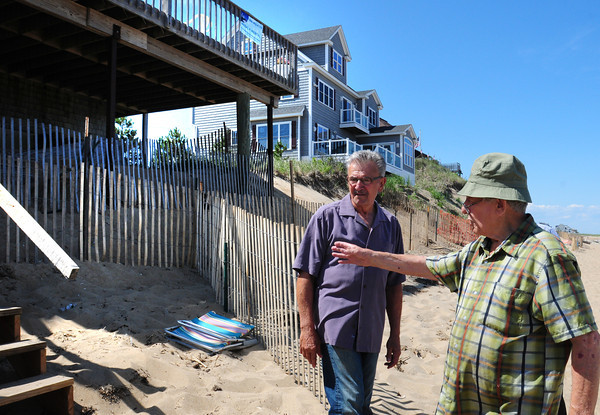 Newbury: Milton Tzitzenipos, right, shows his neighbor Tom Nee the pilings that are 30 feet into the sand that's supporting his porch at 29 Annapolis way. The house in back lost its porch and was itself at danger of collapsing several years ago. Bryan Eaton/Staff Photo