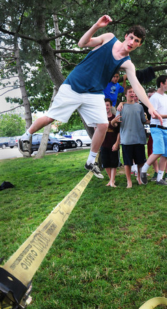 """Newburyport: Mack Donovan, 14, of Newburyport teeters along a """"slack line"""" on Newburyport's waterfront yesterday afternoon. Similar to a tight rope, though it's wider and flatter, it's set up between two trees about a foot off the ground. Bryan Eaton/Staff Photo"""