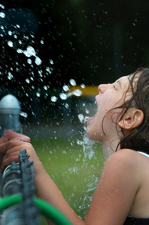 Salisbury: Bryanna Grant, 7, gets a refreshing splash of water during some cooling down fun at the Boys and Girls Club on Monday afternoon. Cooling down will be on people's minds as the weather stays fairly warm throughout the week. Bryan Eaton/Staff Photo