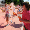 Amesbury: Stacy Kirkland covers a runner with pink powder as the Color Run makes it's way down Main Street in Amesbury Saturday. The estimated 11,000 runners running in the 5k race were covered with colored corn starch ever kilometer. Jim Vaiknoras/staff photo