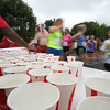 Newburyport: Runners grab water after finishing Tuesday night at the annual Lions Club Race. Jim Vaiknoras/staff photo