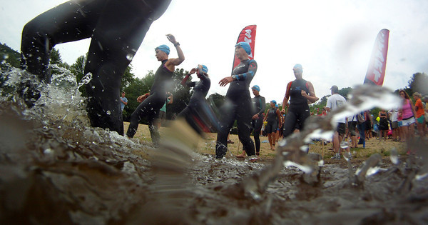 Amesbury: Racers enter the water at the start of the  Dam Triathlon  Saturday at Lake Gardner in Amesbury. Jim Vaiknoras/staff photo