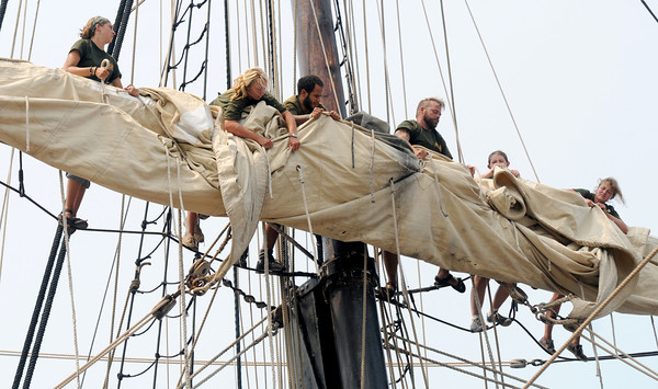 Newburyport:Bounty crew members  furl the sail on the top yard of the main mast as the ship sits along the Newburyport waterfront. Jim Vaiknoras/staff photo