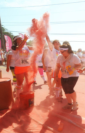 Amesbury: Runners toss pink powder in the air as the Color Run makes it's way down Main Street in Amesbury Saturday. The estimated 11,000 runners running in the 5k race were covered with colored corn starch ever kilometer. Jim Vaiknoras/staff photo
