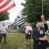 Newburyport General Chairman David Chretien gets some help from Jason Lacroix and Dennis Palazzo as he raises the Yankee Homecoming flag at the Bartlet Mall Sunday. Jim Vaiknoras/staff photo
