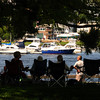 Newburyport: A group of people stay cool in the shade at Market Landing Park as they watch the boats go up and down the Merrimack Sunday afternoon. Jim Vaiknoras/staff photo