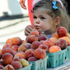 Newburyport: Olivia Bell, 3, of Newburyport, enjoys a peach from the Arrowhead Farm stand at the Newburyport's Farmer's Market at the Tannery Sunday morning. Jim Vaiknoras/staff photo