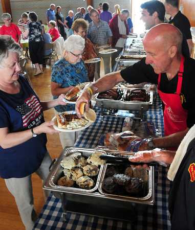 Amesbury: Amesbury Police Chief Mark Gagnon, right, with fellow police and fire department members served senior citizens at their annual cookout for Amesbury Days at Holy Family Parish banquet hall. Bryan Eaton/Staff Photo