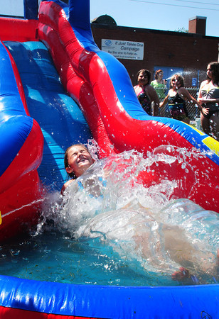 Salisbury: Julia Beauvais, 8, of Amesbury splashes into a pool of water at the end of a waterslide yesterday afternoon at the Boys and Girls Club in Salisbury. The timely activity for cooling off from the heat was part of their Wacky Games Week. Bryan Eaton/Staff Photo