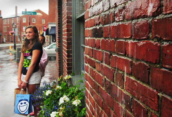 Newburyport: With rain running down the brickwork on State Street in Newburyport sisters Leah Cormier, 13, left, and Cailey, 12, wait for their ride as they left Starbucks and stand under the awning. Though sun returns the next couple days, showers could still appear. Bryan Eaton/Staff Photo