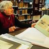 Newburyport: Judith Besancon, volunteer in the archive center at the Newburyport Public Library, leafs through photos by Fran Dalton. Bryan Eaton/Staff Photo