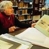 Newburyport: Judith Besancon, volunteer in the archive center at the Newburyport Public Library, leafs through photos by Fran Dalton. Bryan Eaton/Staff Photo