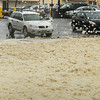 Salisbury: Foam from the ocean is whipped around at Salisbury Beach yesterday next to the Pavilion as people take pictures of the rough waves. Bryan Eaton/Staff Photo