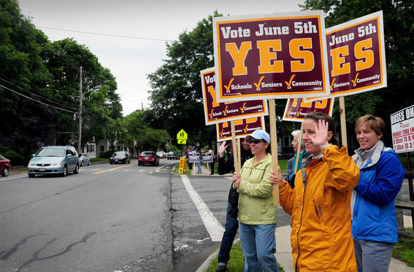 Newburyport: Supporters of the three ballot questions in Newburyport wave to passersby in front of the Bresnahan School yesterday morning. Bryan Eaton/Staff Photo