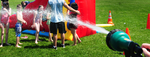 Salisbury: Boys and Girls Club counselor Kristina Andriotkis squirts youngsters as many activities there were held outside due to the record breaking heat. Bryan Eaton/Staff Photo