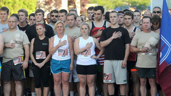 Newburyport: Runners stand at attention during the singing of the National Anthem at the start of the  Derek Hines Flag Day 5K. Thursday nght .  Jim Vaiknoras/staff photo