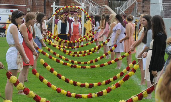 "Newburyport: Students march in under the ""Arch of Roses""  at the Newburyport High Graduation Ceremony at War Memorial Stadium  Sunday. jim Vaiknoras/staff photoa"