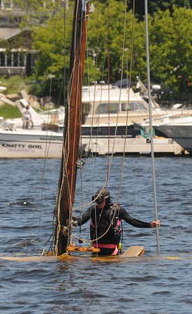 Newburyport: A crew member of TowBoat/US stands near the main mast of  a wooded sailboat that sank in the Merrimack River off the Newburyport waterfront Sunday morning. Jim Vaiknoras/staff photo