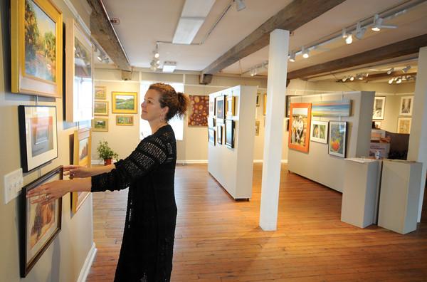 "Newburyport: Kim Litle hangs artwork at Newburyport Art Association for their up coming ""Artful Feast"" <br /> Jim Vaiknoras/staff photo"